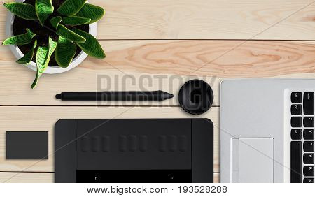 Tools of creativity. Top view of modern laptop graphic tablet with stylus and pot with flower lying on wooden table. Photo editor work space. Modern graphic tablet for retouching. Work art concept