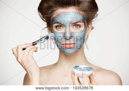 Young beautiful girl in hair curlers smiling looking at camera covering face with mack. Facial treatment. Beauty cosmetology and spa. Copy space.