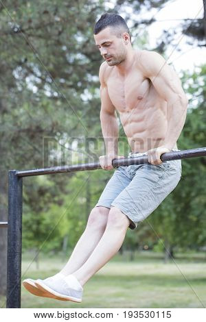 Handsome Young Man With Perfectly Prominent Muscles Doing Exercises On The Horizontal Bar