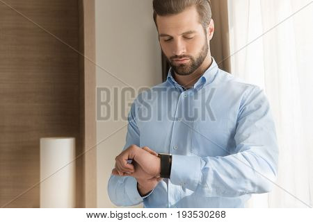 Young male business traveler hotel accomodation checking time