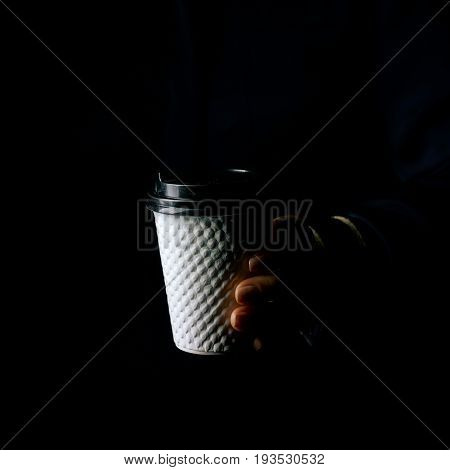 Black Mania. woman hand isolated on black showing paper coffee cup