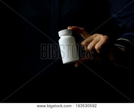 Woman Hand Isolated On Black Showing Bottle Of Medicine