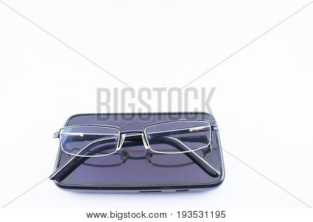 Glasses with increase on a cell phone. White background.