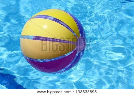 Beachball and swimmingpool vacation close up image