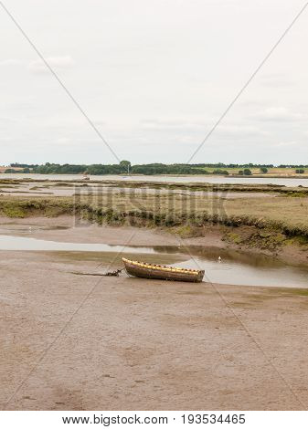 Stock Photo - Single Old Boat In Mud Sea Coast No People Browns