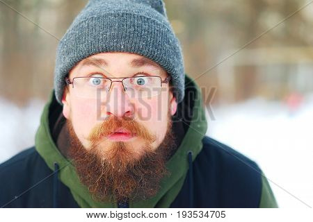 Young bearded guy with glasses and warm winter clothes in shock