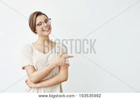 Young beautiful girl in glasses smiling winking looking at camera pointing finger in side over white background. Copy space.