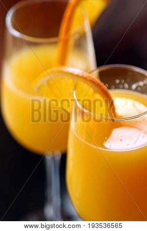 Two mimosas with orange slice garnishes close up