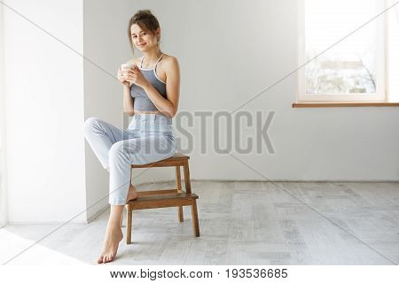 Young tender brunette girl smiling holding cup looking at camera sitting on chair over white wall early in morning. Copy space.