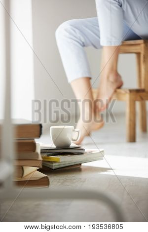 Close up photo of books and cup of coffee lying on floor. Girl's legs on chair background. Copy space.