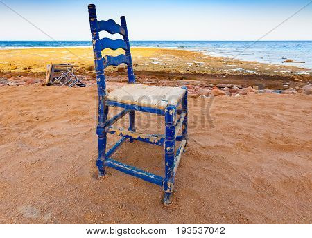 Egypt the Red Sea. Dahab. The edge of the surf algae and corals. Landscape. The colors are blue yellow green red. In the frame the old retro chair is blue