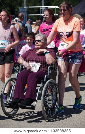SOUTHAMPTON UK - July 2 2017: Race for Life women run and walk to raise money for Cancer Research charity in Southampton UK.Woman in a wheelchair bing pushed in wheelchair during race.