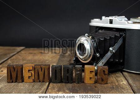 word memories in vintage wooden letterpress type with old camera on rustic wood