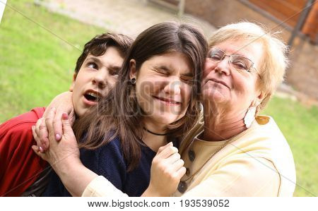 grandma with grandchildren close up cuddle photo on summer background