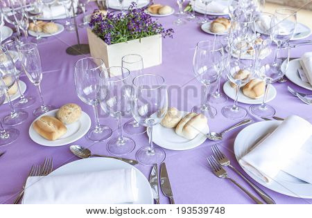 Wedding table decorated on mauve color. Centerpiece full of violet flowers in the middle