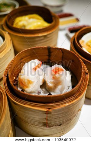 Close up Dim Sum steamed chinese dumpling topping with imitated crab in a stack of bamboo baskets. Traditional chinese cuisine in hot steam.