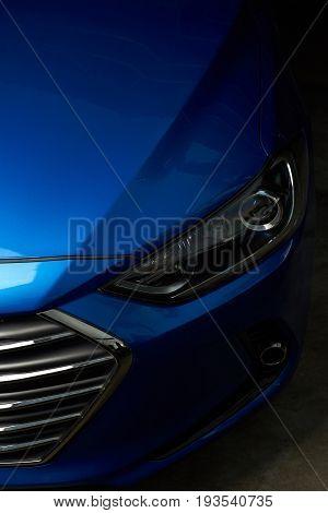 Elegant car headlight background. Blue modern shiny car bonnet