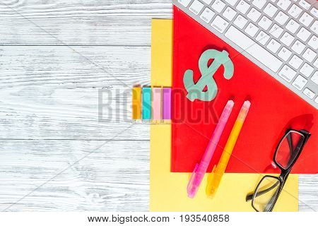 Scholarship or grant for education concept. Dollar sign, paper and keyboard on wooden table top view.