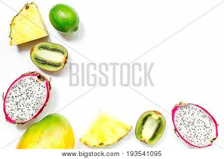 Pieces of exotic fruits. Dragonfruit, pineapple and kiwi on white background top view.