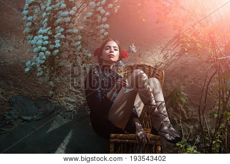 beautiful woman drink wine in the garden sitting on chair
