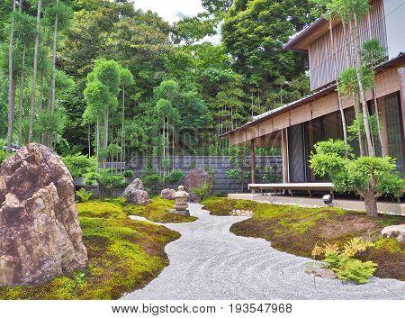 Gravel path, stone lantern, stones and wooden building in Japanese garden inside Hase-dera Temple, city of Kamakura, Kanagawa Prefecture, Japan.