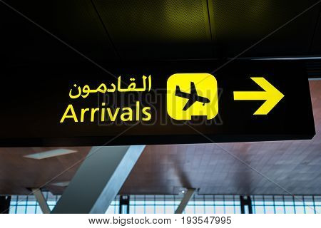 Airport arrival sign - international flight arrival information sign at airport in English and Arabic