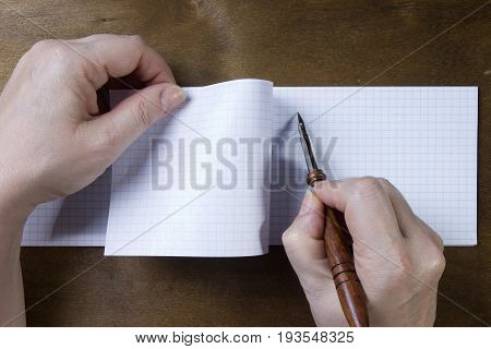 Hand writing in a note book on a wooden background