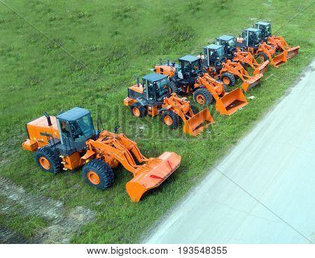 New shiny and modern orange excavator machines. Construction industry machinery.