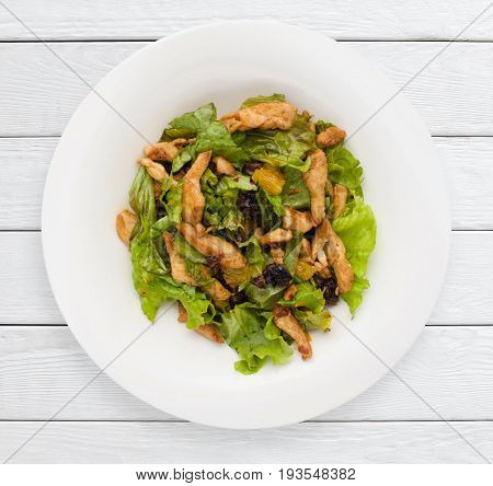 Salad with prunes and fried chicken fillet top view. Healthy food, sport meal, lunch dish concept. White wooden planks background.