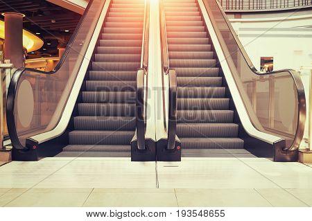 Escalator step and white tile floor inside building.