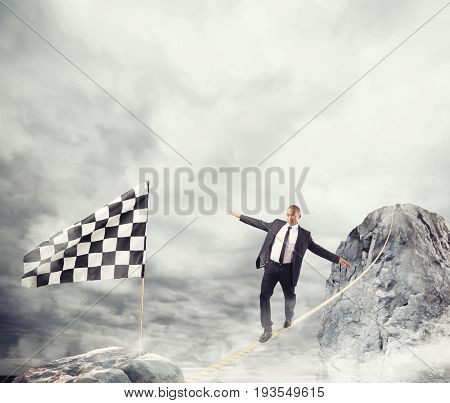 Business concept of businessman who overcome the problems reaching the finish line on a rope