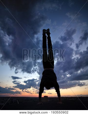 Silhouette of a man against a background of clouds and golden sunset. He stands upside down on the roof. Parkour in the evening.