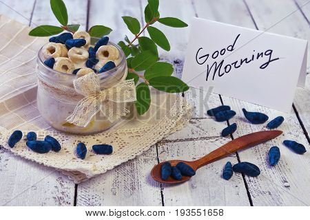 Healthy snack with text good morning on the note and spoon with honeysuckle berries on vintage napkin. Morning still life with healthy breakfast. Summer vintage background, vegetarian and vegan concept