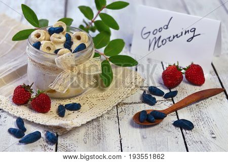 Dry breakfast cereal with strawberries and honey berries and with good morning text note on planks. Morning still life with healthy breakfast. Summer vintage background, vegetarian and vegan concept