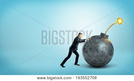 A tiny businessman in side view pushing at a giant round bomb with a lit fuse on blue background. Business motivation. Unexpected measures. Sales bomb.