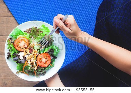 Overhead view of yoga woman eating fresh salad Healthy eating and Working out concept