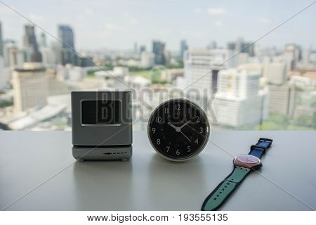 analog and digital modern clock with women watch on white table