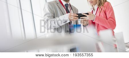 Business people using smart phone in convention center