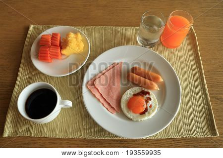 Set of american breakfast on table fried egg ham and sausage with fresh fruits black coffee orange juice and drinking water.