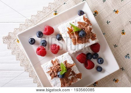 Pieces Of Chocolate Cake With Berries Close-up On A Plate. Horizontal Top View