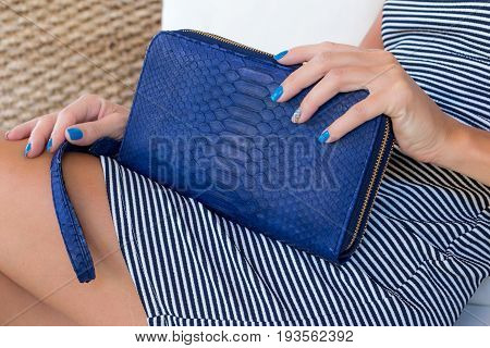 Luxury snakeskin wallet purse in woman hands. Bali island, handmade purse.
