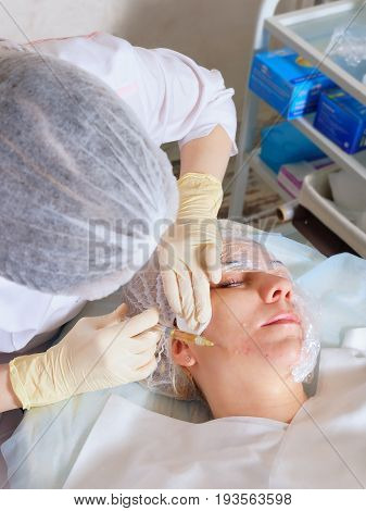 Cosmetic injection with hyaluronic acid. Mesotherapy. Beautician makes an injection into woman's face.