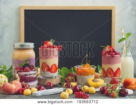 Clean eating ideas for breakfast or snack. Assortment of  berry fruit  smoothies, juices and chia seeds pudding in front of a chalkboard . Concept of healthy eating.. Concept of healthy eating.