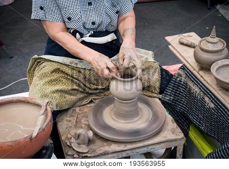 Senior Potter's Hands Shaping Traditional Clay Pot