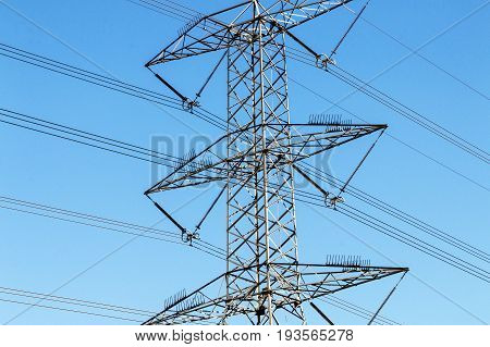 Close Up Of Electric Pylons  Powerlines And Blue Sky