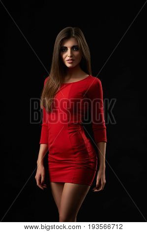 Studio portrait of a stunning beautiful young dark haired woman wearing sexy red dress posing on dark background beauty seductive seduction sexuality femininity confidence concept.