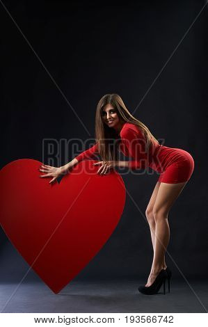 Happy young beautiful woman wearing sexy red dress posing seductively with a big read heart symbol sign love valentines day celebration passion concept.