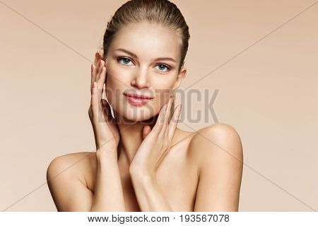 Portrait of young woman with beautiful eyes. Attractive woman looks at the camera on beige background. Youth and skin care concept