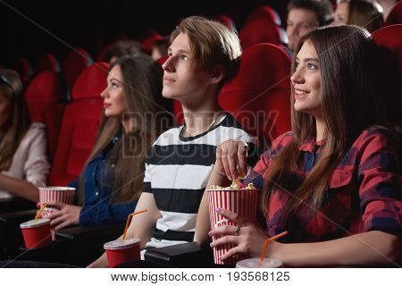Young woman smiling sitting next to her male friend at the cinema enjoying a movie eating popcorn entertainment emotions people lifestyle happiness positivity leisure spectators comedy.