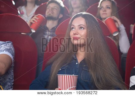 Gorgeous young woman smiling enjoying watching a movie at the local cinema spectator premiere film happiness leisure activity recreation people lifestyle concept.